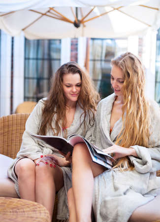 toweling: Two young women relaxing in the spa resort reading the magazine wearing toweling robes