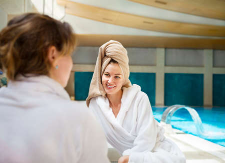 toweling: Two young women relaxing by the poolside wearing toweling robes Stock Photo