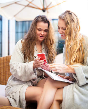 selfy: Two young women relaxing in the spa resort looking to mobile phone wearing toweling robes Stock Photo