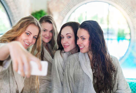toweling: Four young women relaxing in the spa resort doing selfy wearing toweling robes Stock Photo