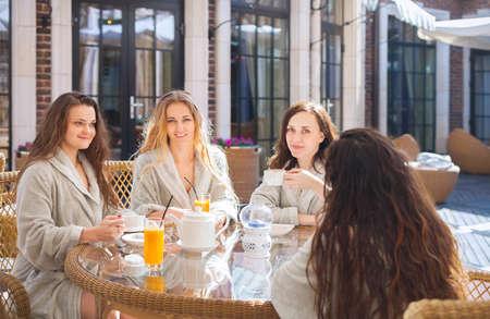 Quatre jeunes femmes heureuses buvant du thé à la station thermale