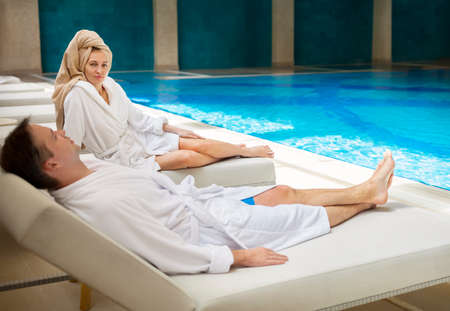 toweling: Young couple relaxing by the poolside wearing toweling robes