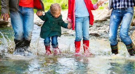Gelukkige familie met twee kinderen dragen regenlaarzen springen in een bergrivier