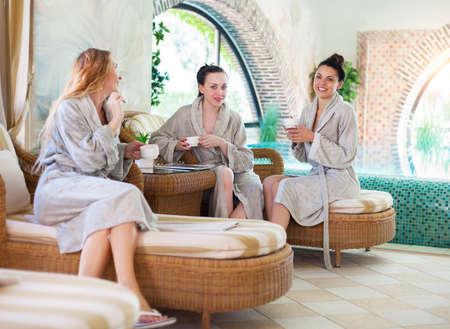Drei junge glückliche Frauen trinken Tee in Kurort