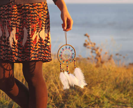female shaman: Brunette woman with long hair holding dream catcher in her hands Stock Photo