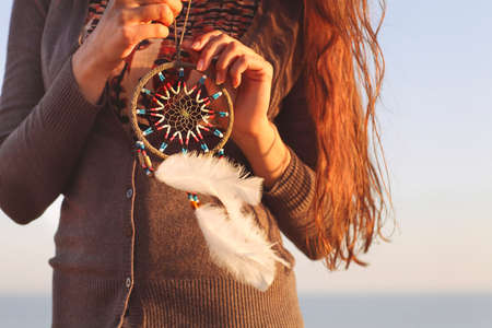 Brunette woman with long hair holding dream catcher in her hands Stockfoto