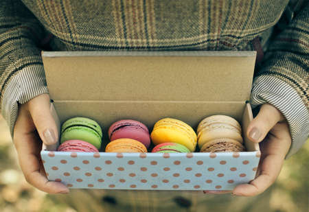 raspberry dress: Woman wearing coat holding box with colorful French macaroons in her hands