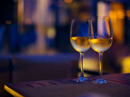 Two glasses of the white wine in the night. Close up. DOF