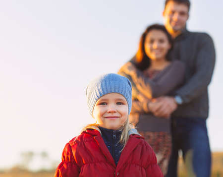 person outdoors: Portrait of the little girl with a funny hat outdoors and man and woman holding hands of smiling at the background. Family leisure outdoors concept