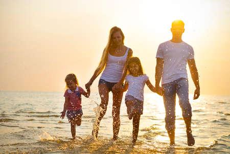 여행: 일몰 해변에서 실행하는 행복 한 젊은 가족 재미. 톤의 사진. 가족 개념을 여행. 아무 효과가 없습니다 - 진짜 일