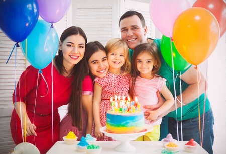 children birthday: Portrait of a family celebrating birthday of their little daughter. Family fun concept Stock Photo