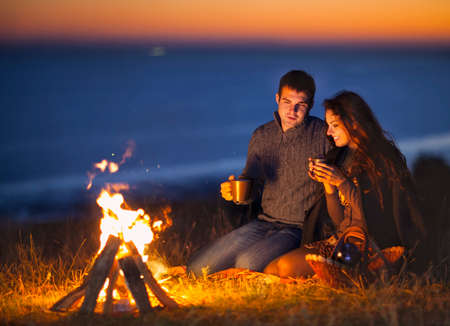 Portrait of the happy couple sitting by fire on autumn beach at the night. Stock Photo
