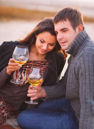 fall winter: Young happy couple enjoying picnic with white wine on the beach together