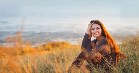 feeling good: Portrait of the beautiful brunette woman at the windy autumn day relaxing on coast feeling good