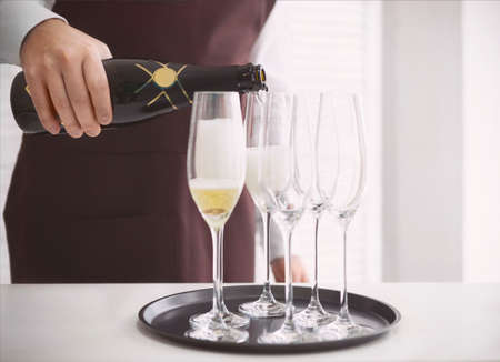 professional flute: Professional male waiter in uniform pouring champagne into a flute. DOF. Natural light. Photo in motion Stock Photo