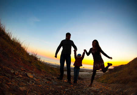 get out: Silhouette of two happy adults and a child at the coast Stock Photo