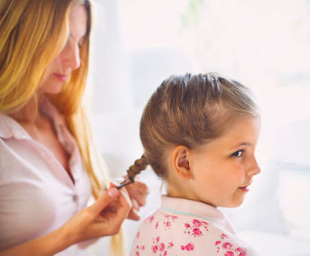 eight years old: Mother hairdressing her preteen daughter at home. Close up Stock Photo