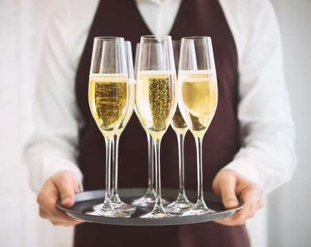 charolas: Camarero masculino profesional en uniforme que sirve champán. DOF. La luz natural. Fotos en movimiento