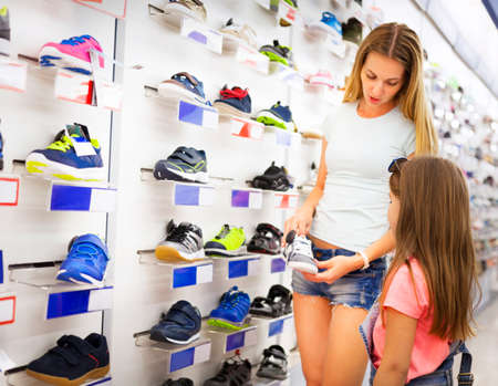 Mother and daughter shopping for shoes choicing sneakers Stock Photo