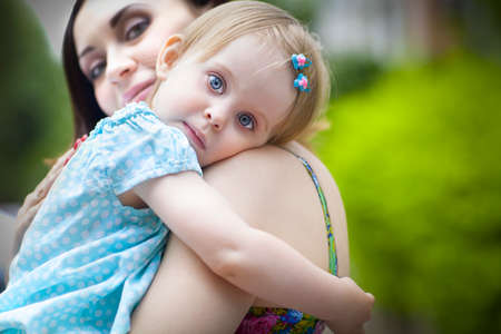 sprightly: Portrait of a beautiful young mother with daughter in summer park