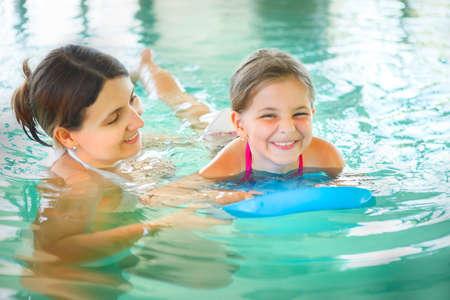 母は彼女の小さな娘を屋内スイミング プールで泳ぐことを学ぶします。一緒に楽しんで。子供の水泳の概念。