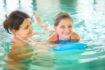 Mother learning to swim her little daughter in an indoor swimming pool. Having fun together. Kids swimming concept.