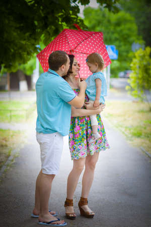 family planning: Young happy family under umbrella on sidewalk Stock Photo