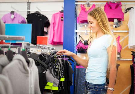 ropa deportiva: Mujer joven de compras para la ropa deportiva en el centro comercial
