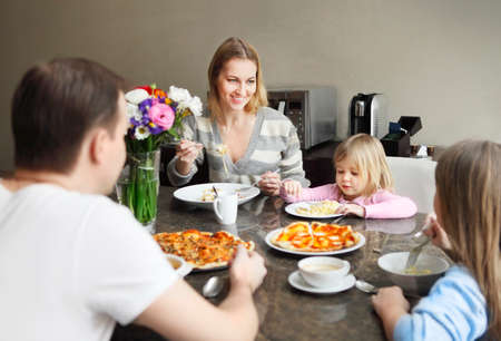 spaghetti: Happy family in kitchen having dinner and laughing Stock Photo