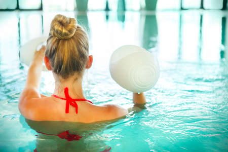 Blond young woman doing aqua aerobics with foam dumbbells in swimming pool at the leisure centre Stockfoto