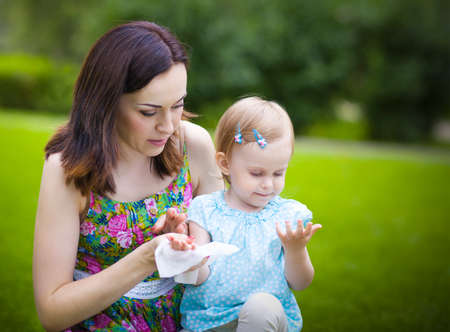 Mother using wet wipes for her daughter on white park background Stockfoto