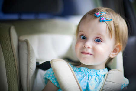 Portrait of a happy little baby girl in the car seat