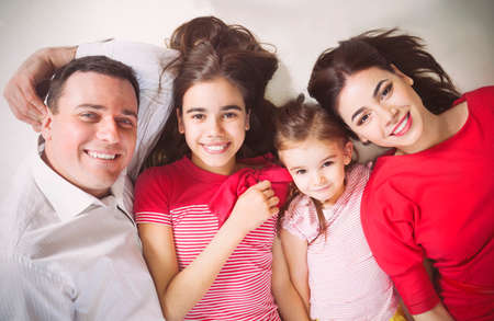 latin family: Portrait of a happy young family with kids lying on a floor at home