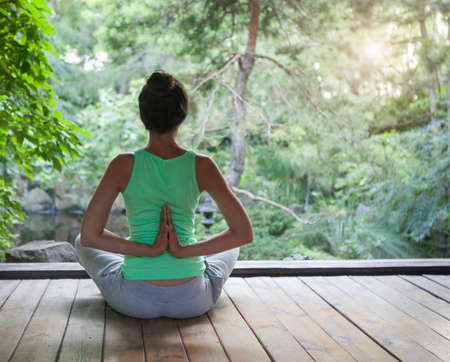 Young woman doing yoga asana in the evening outdoors
