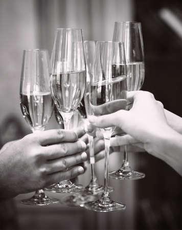 felicitaciones: Celebración. Las personas titulares de copas de champán que hacen una tostada. DOF. Luz natural. Fotos en movimiento. Imagen en blanco y negro Foto de archivo