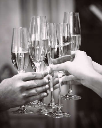 congratulation: Celebration. People holding glasses of champagne making a toast. DOF. Natural light. Photo in motion. Black and white image Stock Photo