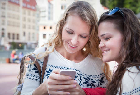 web browsing: Two happy women friends sharing social media in a smart phone outdoors in a city. Two young women looking at mobile phone together while standing outdoors city. Drink coffee and discuss news