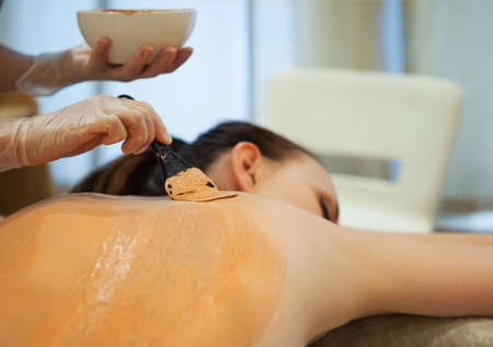 body mask: Beautiful relaxed woman having clay body mask apply by beautician in the spa salon