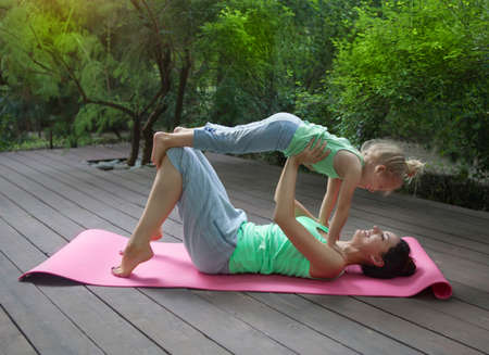 mum and daughter: Mother and daughter doing exercise practicing yoga outdoors. Healthy lifestyle
