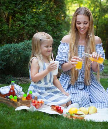 limonada: Feliz joven madre y su hija que tienen comida campestre en el parque de verano