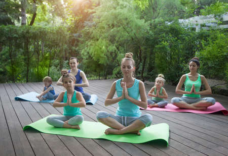 meditating: Group of mothers and daughters doing exercise practicing yoga outdoors. Healthy lifestyle Stock Photo