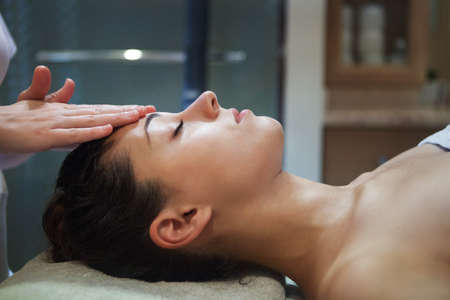 masaje facial: Masajista haciendo masaje facial de una mujer adulta en el salón del balneario