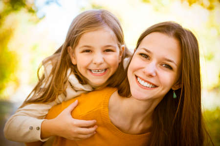 Two cheerful sisters playing in the park in warm autumn day Stock Photo