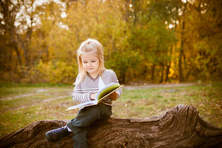 little table: Cute little girl reading a book in autumn park