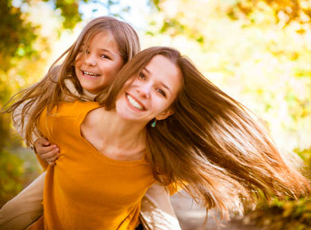 Two cheerful sisters playing in the park in warm autumn day Stockfoto