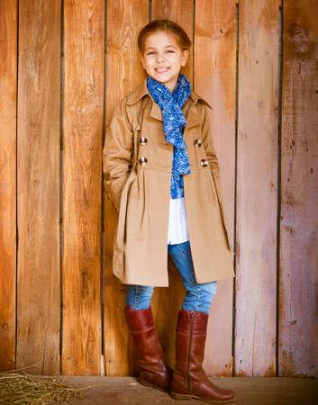 botas: Niña que desgasta la ropa lindas del otoño de pie sobre fondo de madera Foto de archivo