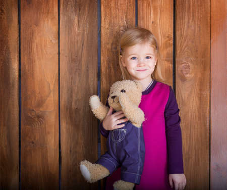 Portrait of the little smiling girl with toy bear. Close up