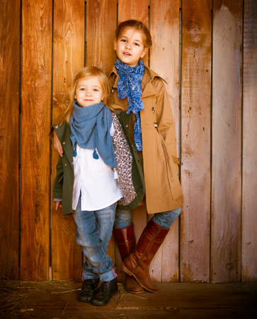winter fashion: Cute little sisters wearing autumn  clothes posing over wooden background