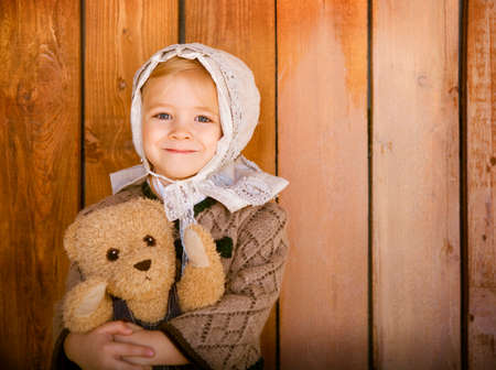 naptime: Portrait of the little smiling girl wering vintage clothes with toy bear. Close up Stock Photo