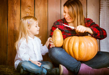 Mother and her little daughter carving Halloween pumpkins together